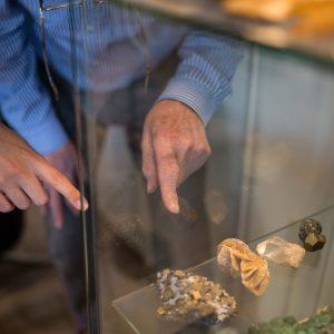 handen wijzen naar mineralen in vitrinekast