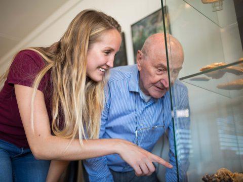 student en senior wijzen naar mineralen in vitrinekast